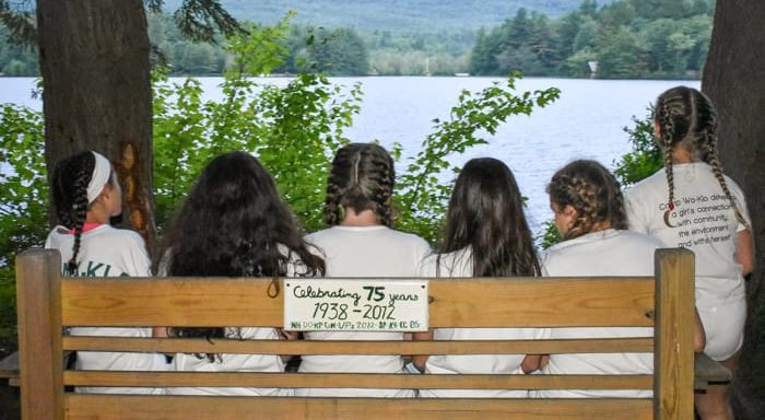 Girls sitting on a bench looking out at lake