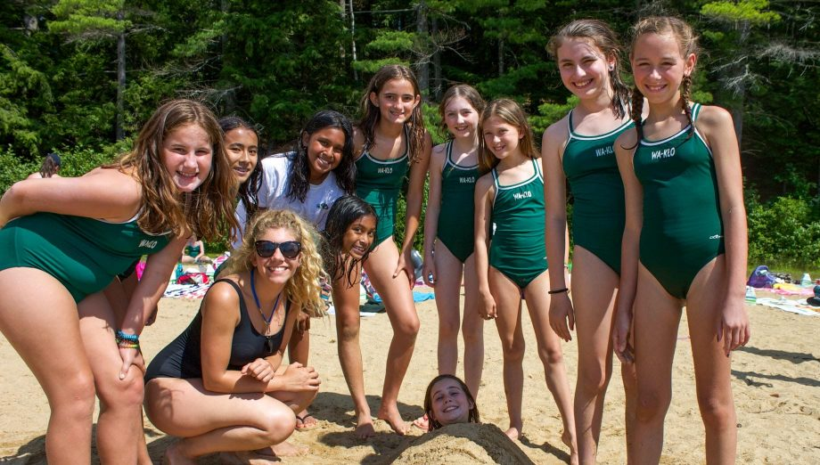 Group of girls at the beach with a friend buried in the sand