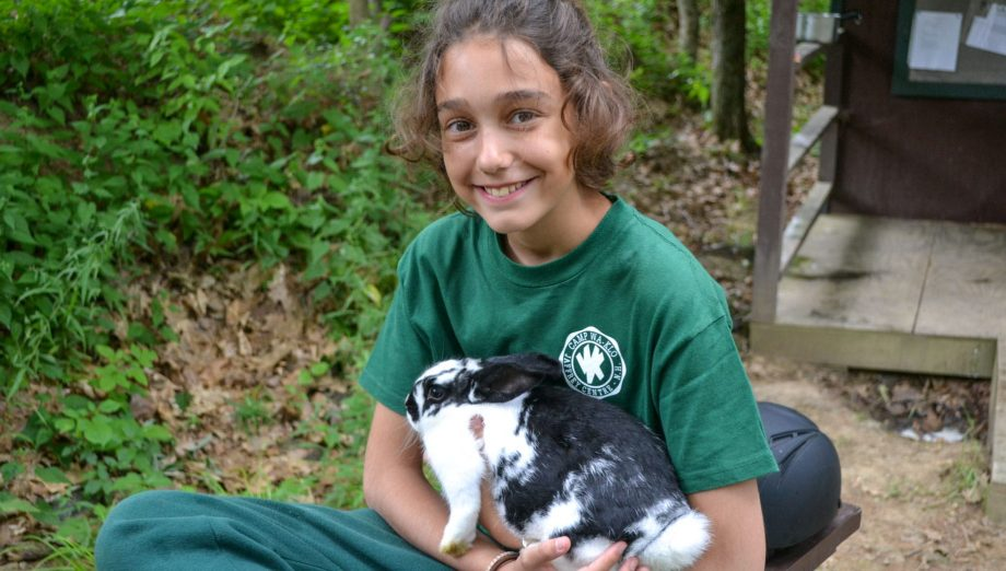 Camper holding bunny at pet care