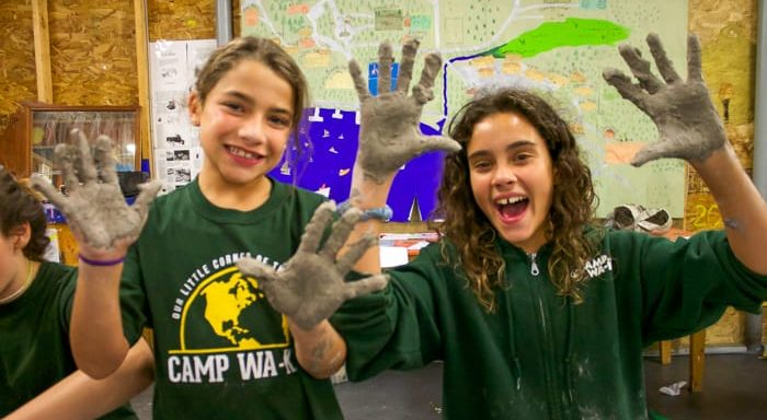 Two campers with clay on their hands