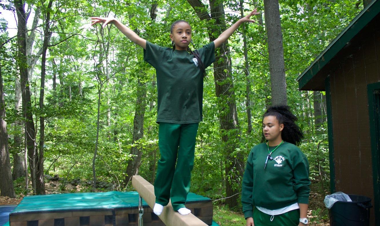 Staff helping camper at gymnastics