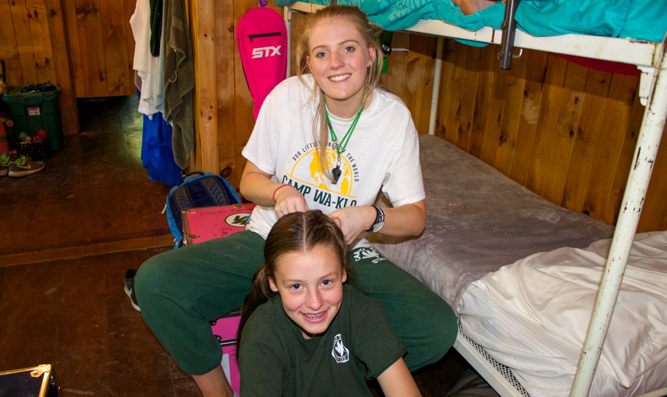 Staff doing camper's hair in bunk
