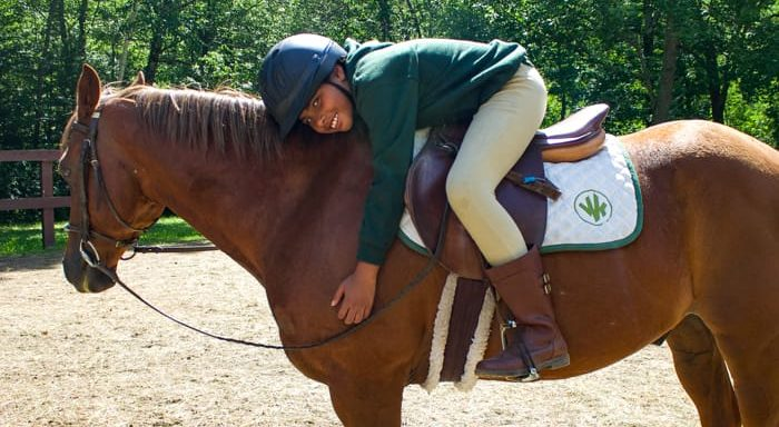 Girl horseback riding and hugging horse