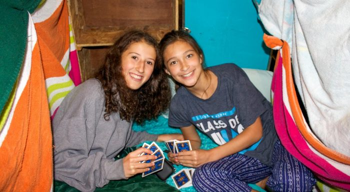 Two girls playing cards in their bunk
