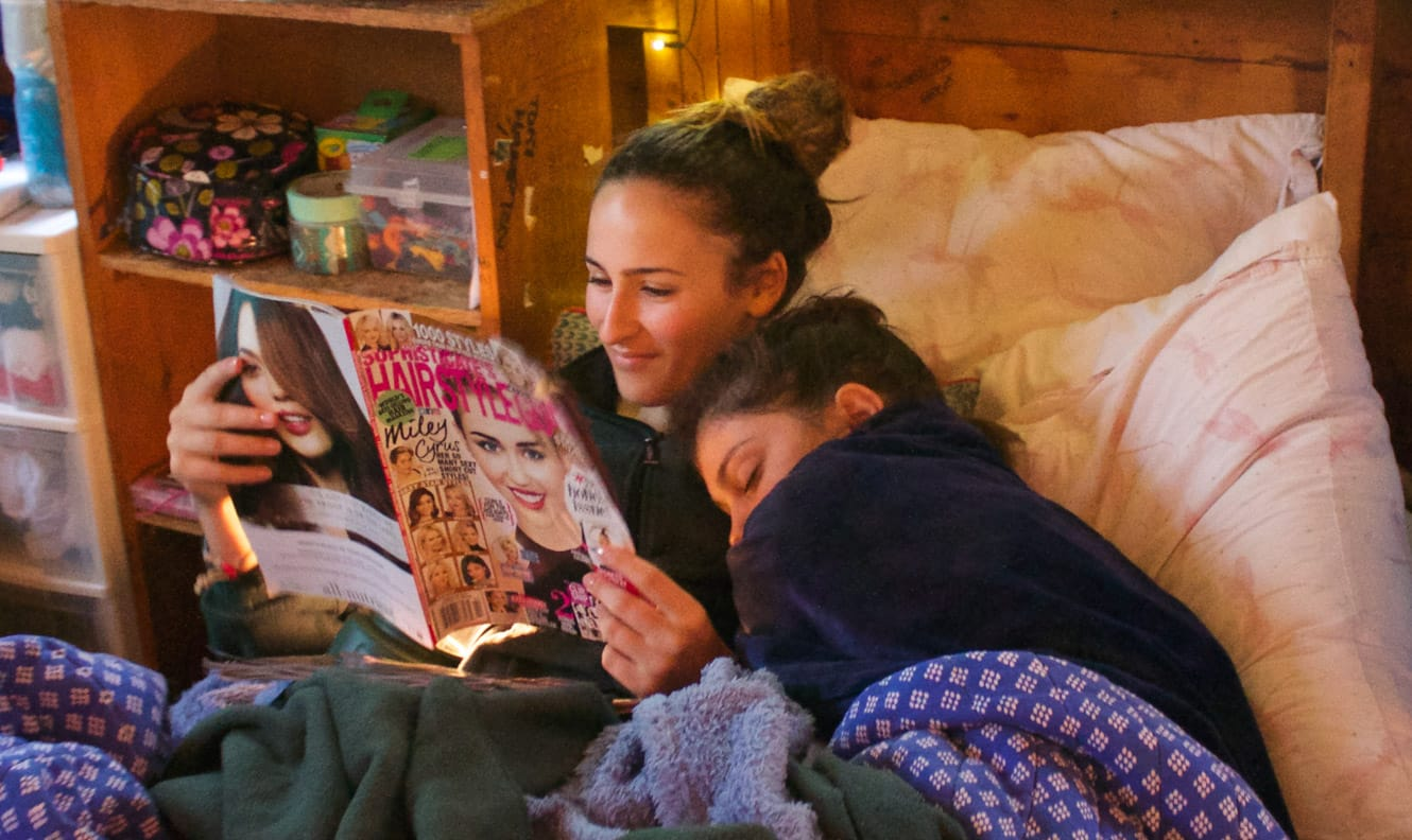 Staff reading while camper sleeps