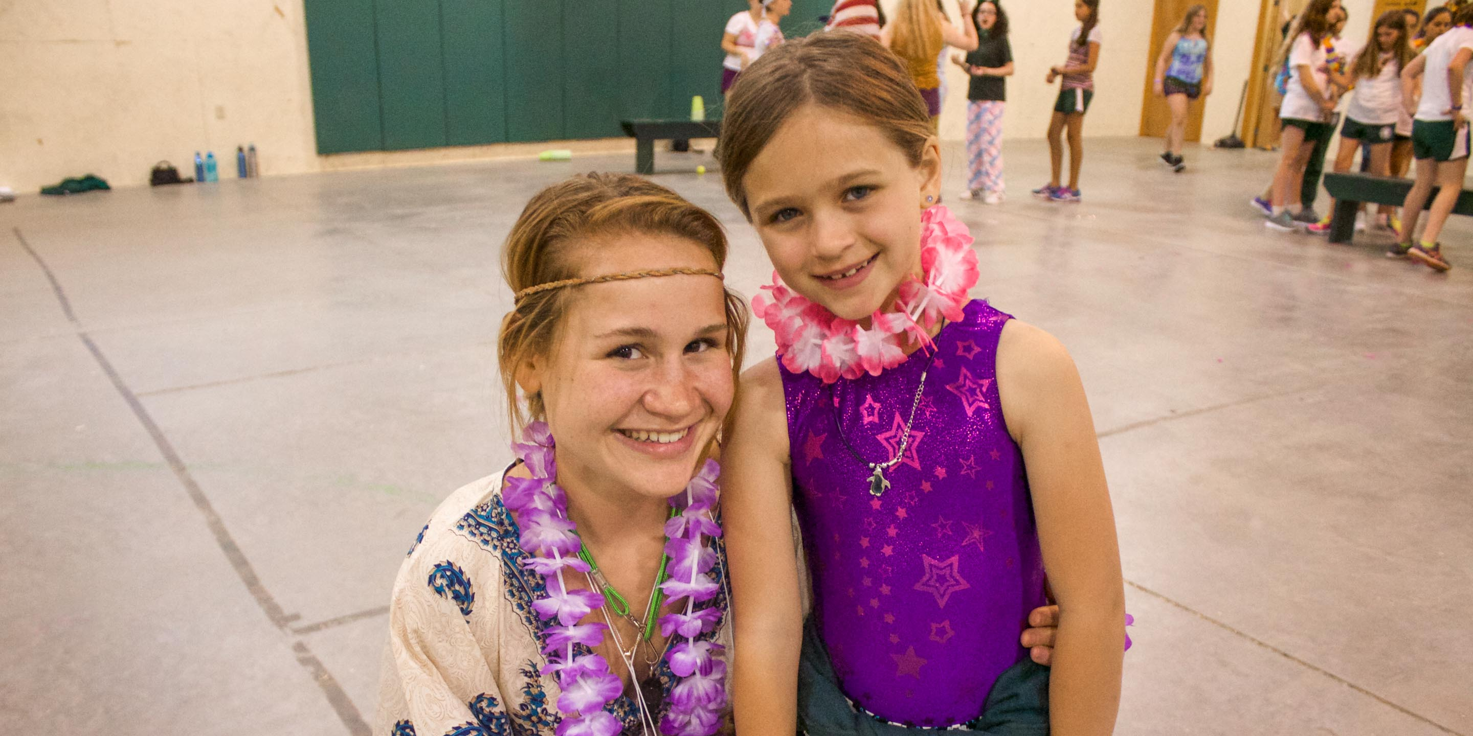 Staff with young camper dressed in Hawaiian leis
