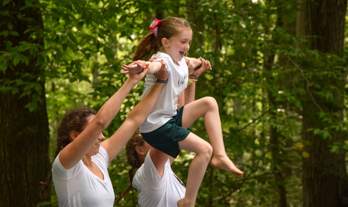 Staff lifting girl in air