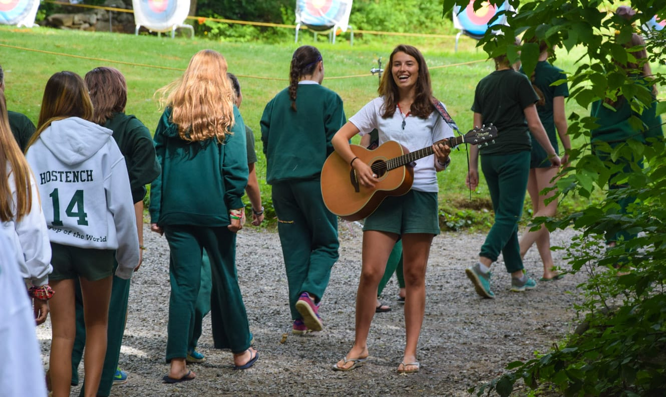 Staff playing guitar for campers walking by