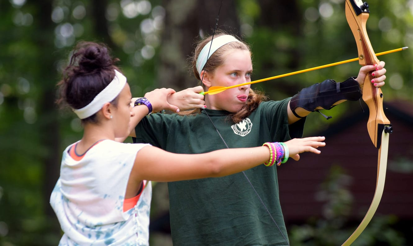Staff helping camper at archery
