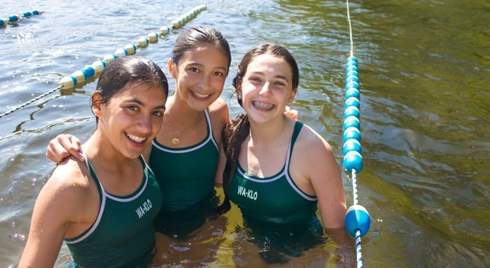 Three girls swimming in lake