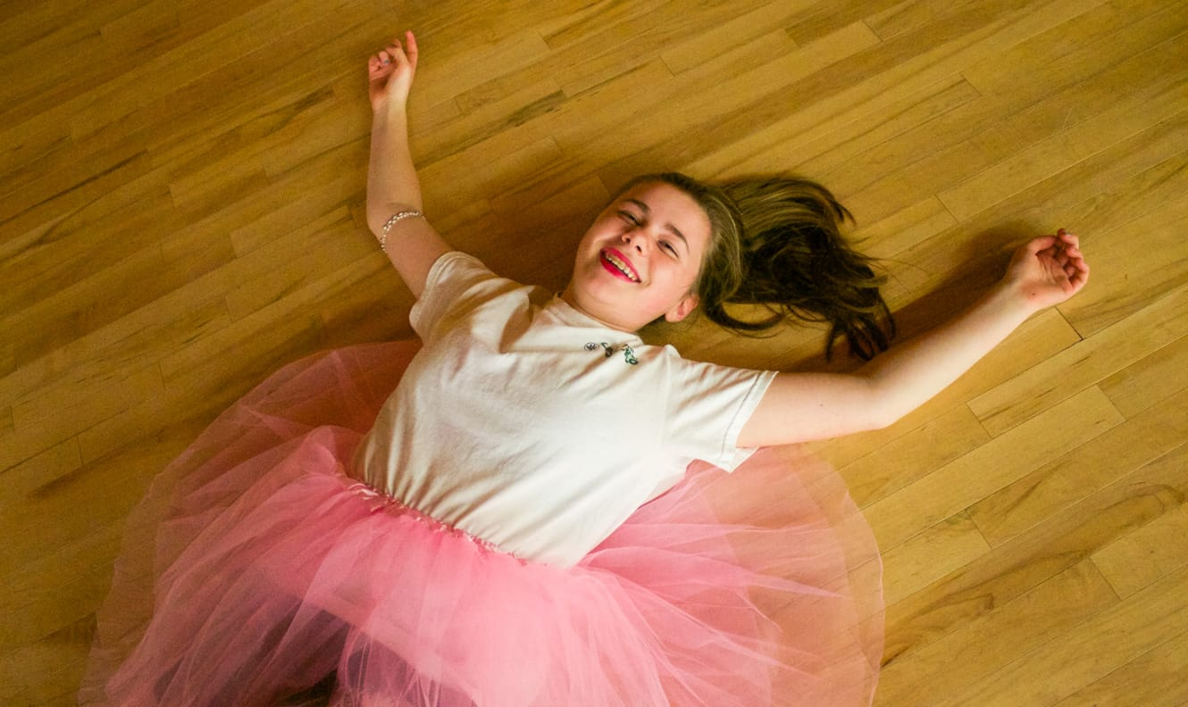 Girl in tutu laying on floor